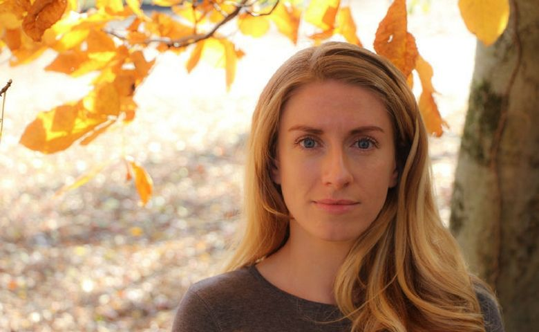 Composer Emma O'Halloran stands in front of a background of autumn leaves